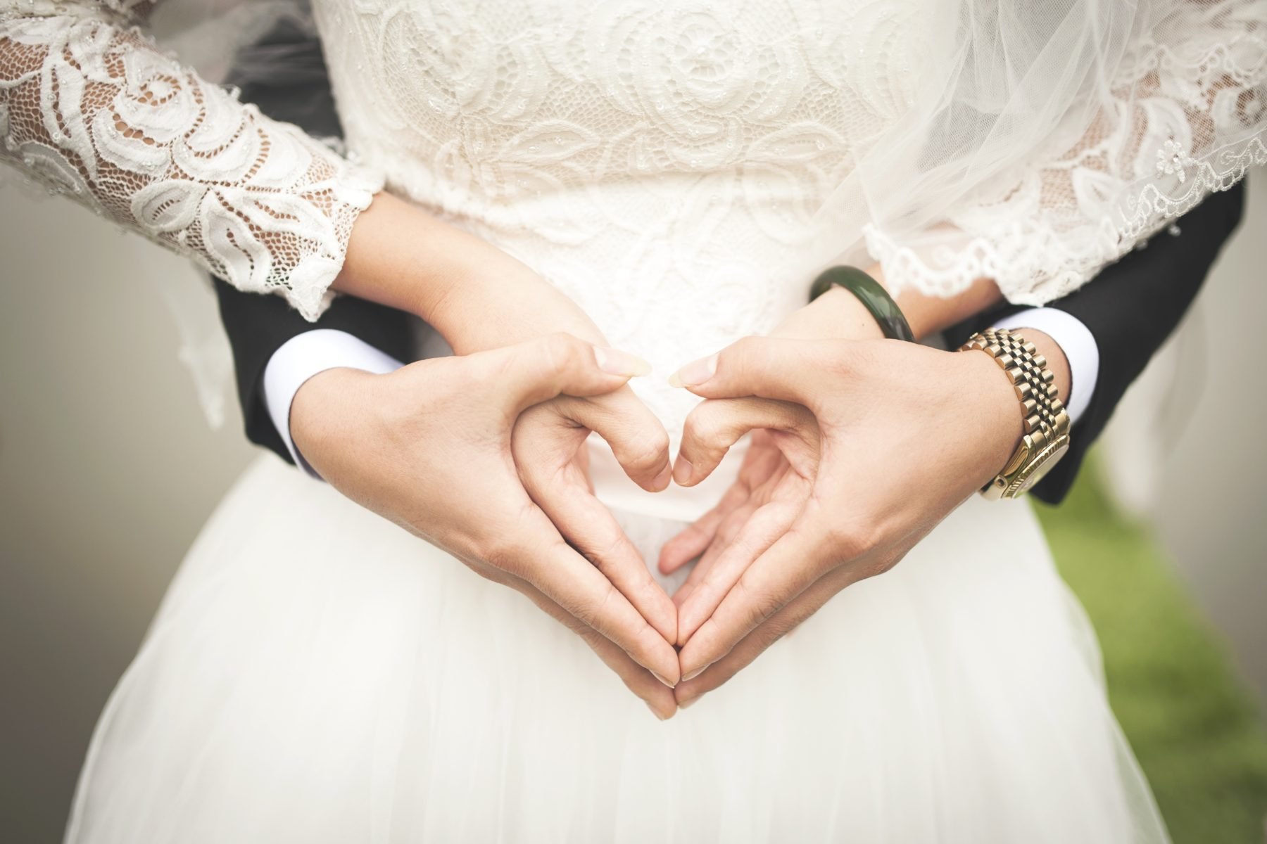 Wedding couples hands creating shape of a heart